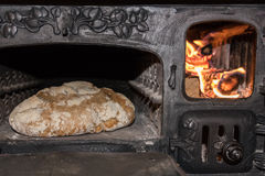 Baking bread in a cast iron stove. Baking bread in an old cast iron stove Stock Photo