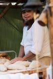 Baking bread. A man with a beard bakes bread royalty free stock photos