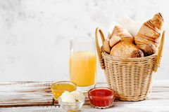 Baking breakfast croissants and bun in basket with orange juice, honey, butter, raspberry jam on white wood table. Baking breakfast croissants and bun in basket Stock Photo