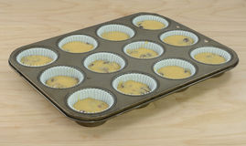 Baking breakfast muffins in muffin pan royalty free stock image