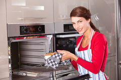 Baking a cake. Brunette taking her freshly baked cake out of the oven Stock Image