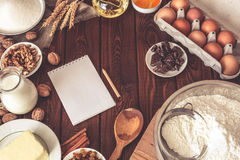 Baking cake in rural kitchen, dough recipe ingredients : eggs, flour, milk. Butter, oil, walnuts and raisins on vintage wood table from above. Rustic Royalty Free Stock Photos