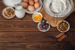 Baking cake in rural kitchen, dough recipe ingredients : eggs, flour, milk. Walnuts and raisins on vintage wood table from above. Rustic background with free Royalty Free Stock Photos