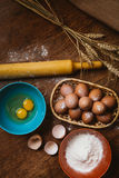 Baking cake in rural kitchen - dough  recipe ingredients eggs, flour, sugar on vintage  wooden table from above. Stock Images