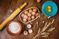 Baking cake in rural kitchen - dough  recipe ingredients eggs, flour, sugar on vintage  wooden table from above. Stock Image