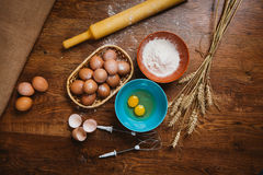 Baking cake in rural kitchen - dough  recipe ingredients eggs, flour, sugar on vintage  wooden table from above. Royalty Free Stock Photo