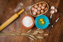 Baking cake in rural kitchen - dough  recipe ingredients eggs, flour, sugar on vintage  wooden table from above. Royalty Free Stock Photography