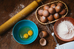Baking cake in rural kitchen - dough  recipe ingredients eggs, flour, sugar on vintage  wooden table from above. Stock Photo