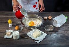 Baking cake in rural kitchen. Baking cake on wooden table in rural kitchen Royalty Free Stock Image