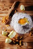 Baking cake in rustic kitchen. Some of recipe ingredients eggs, flour, apple, raisins on wood table. View from above Royalty Free Stock Photos