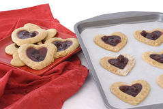 Baking Cherry Heart Cookies. Unbaked sheet of cherry heart cookies next to a red plate of baked cookies setting against a red napkin Royalty Free Stock Image