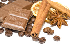 Baking chocolate. An assortment of some of the more popular coffee flavorings :  cinnamon sticks, chocolate, dried orange, anise with roasted coffee beans Royalty Free Stock Image