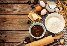 Baking chocolate cake - recipe ingredients on vintage wood. Baking chocolate cake in rural or rustic kitchen. Dough recipe ingredients (eggs, flour, milk, butter Stock Photo