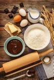 Baking chocolate cake - recipe ingredients on vintage wood. Baking chocolate cake in rural or rustic kitchen. Dough recipe ingredients (eggs, flour, milk, butter Stock Photo
