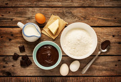 Baking chocolate cake - recipe ingredients on vintage wood. Baking chocolate cake in rural or rustic kitchen. Dough recipe ingredients (eggs, flour, milk, butter Royalty Free Stock Photo