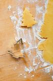 Baking Christmas cookies. Dough, cookie cutter and flour on wooden table Stock Images