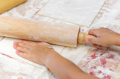 Baking Christmas cookies, child hands cuts dough Stock Photography