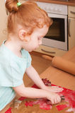 Baking Christmas cookies. Little girl baking cutting pastry for Christmas cookies royalty free stock photography