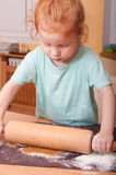 Baking Christmas cookies. Little girl baking rolling pastry for Christmas cookies stock images