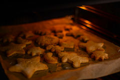 Baking christmas cookies in oven Royalty Free Stock Images