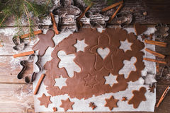Baking Christmas Cookies. Roll Out The Dough To Cut Out Stars And Gingerbreadman On A Wooden Background. Royalty Free Stock Photography