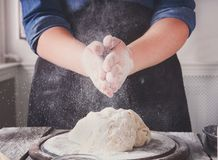 Woman baker knead and sprinkle yeast dough with eggs and flour Royalty Free Stock Photo
