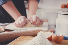 Woman baker knead yeast dough with eggs and flour. Baking concept. Flour, milk, and eggs on wooden cutting board, pastry ingredients. Cropped image of Royalty Free Stock Images