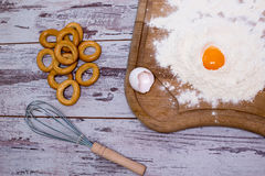 Baking concept. Sprinkled flour and eggs on wooden cutting board, cooking ingredients. Prepare for making yeast dough. Top view, c Stock Image