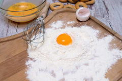 Baking concept. Sprinkled flour and eggs on wooden cutting board, cooking ingredients. Prepare for making yeast dough. Top view, c Stock Photography