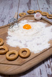Baking concept. Sprinkled flour and eggs on wooden cutting board, cooking ingredients. Prepare for making yeast dough. Top view, c Stock Photo