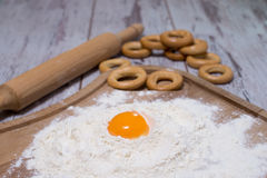 Baking concept. Sprinkled flour and eggs on wooden cutting board, cooking ingredients. Prepare for making yeast dough. Top view, c Royalty Free Stock Photography