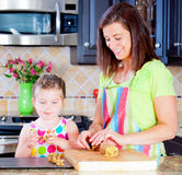 Baking cookies. Mother and daughter putting cookie dough onto baking sheet in kitchen Stock Photos