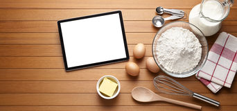 Baking Cooking Tablet Background. A computer tablet with various baking ingredients and utensils on a warm wood background Royalty Free Stock Image