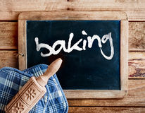 Baking in a country kitchen. Country kitchen with a decorative carved wooden rolling pin with a floral pattern on oven gloves lying on an old vintage school Stock Images