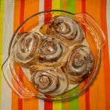 Baking Dish Cinnamon Rolls. Baking dish of cooked and iced cinnamon rolls on a colorful place mat royalty free stock photo