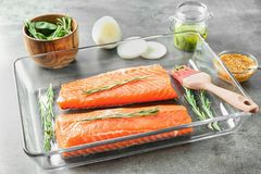 Baking dish with fresh raw salmon fillet. Ready for marinating on table Royalty Free Stock Image
