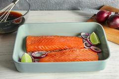 Baking dish with fresh raw salmon fillet. And soy marinade in bowl on table Royalty Free Stock Photo