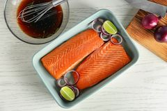 Baking dish with fresh raw salmon fillet. And soy marinade in bowl on table Stock Photo