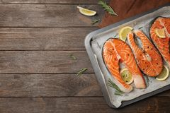 Baking dish with fresh raw salmon steaks. And seasonings on wooden background, top view Royalty Free Stock Image