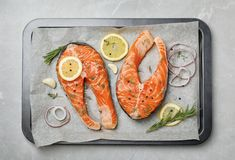 Baking dish with fresh raw salmon steaks. And seasonings on gray background, top view Royalty Free Stock Photo