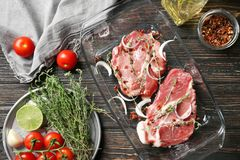 Baking dish with fresh raw steaks and vegetables. On table Stock Photography