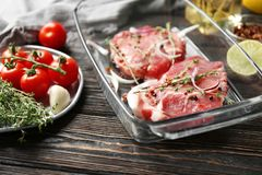 Baking dish with fresh raw steaks and vegetables. On table Stock Photo