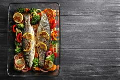 Baking dish with two tasty fish and garnish. On grey background Royalty Free Stock Image