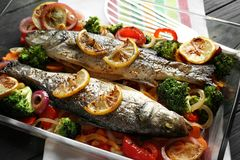 Baking dish with two tasty fish and garnish. On grey background Royalty Free Stock Photos
