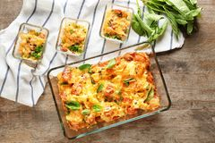 Baking dishes with delicious sausage casserole. On table Stock Photo