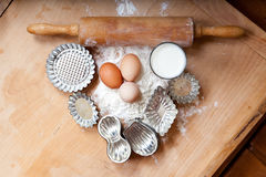Baking dough on old wooden board, with retro rolling pin and vintage cookie cutters Royalty Free Stock Photography
