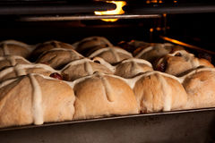 Baking fresh homemade cross buns in oven. Tray of fresh hot cross buns baking in oven Royalty Free Stock Images