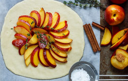 Baking a fruit pie with peaches, nectarines. The ingredients on the table - dough, peaches, nectarines, sugar, cinnamon, thyme. Selective focus royalty free stock photography