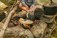 Baking frying bread on an open fire outside stock images