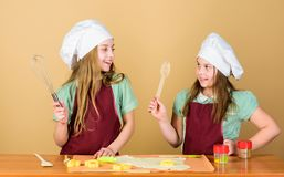 Baking ginger cookies. Girls sisters having fun ginger dough. Homemade cookies best. Kids baking cookies together. Kids. Aprons and chef hats cooking. Family stock photo